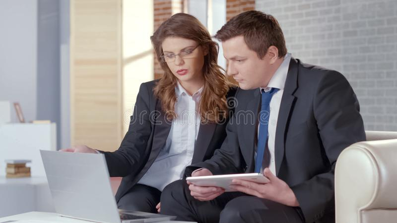 Geschäftsfrau und Mann, die Probleme im Start, aufpassendes Projekt auf Laptop besprechen lizenzfreie stockfotos