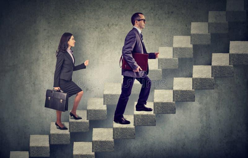 Geschäftsfrau und Mann mit Aktenkoffer eine Treppenhauskarriereleiter steigernd lizenzfreie stockfotografie