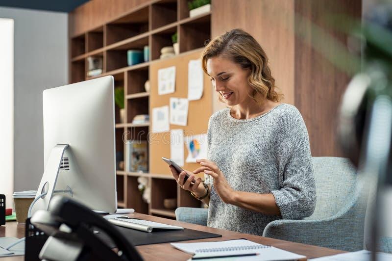 Geschäftsfrau unter Verwendung des Smartphone beim Arbeiten lizenzfreies stockfoto
