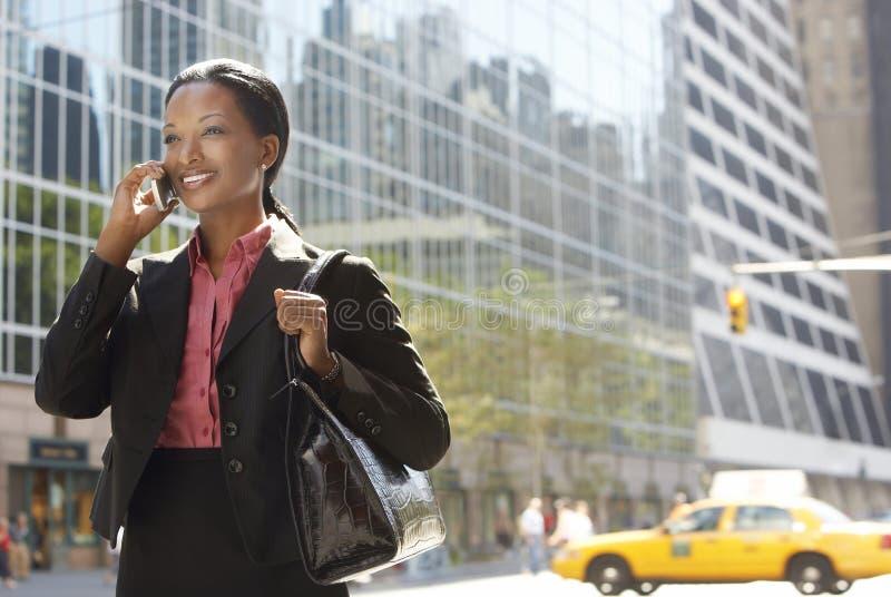 Geschäftsfrau Using Mobile Phone auf Straße stockfotografie