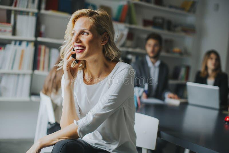 Geschäftsfrau Using Mobile Phone im Büro lizenzfreies stockbild