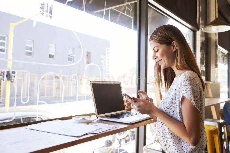Geschäftsfrau Using Phone Whilst, das in der Kaffeestube arbeitet stockbild