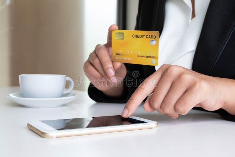Geschäftsfrau-Verbraucherholding Kreditkarte und Smartphone für das on-line-Einkaufen und Zahlung schließen einen Kauf im Interne stockfotografie