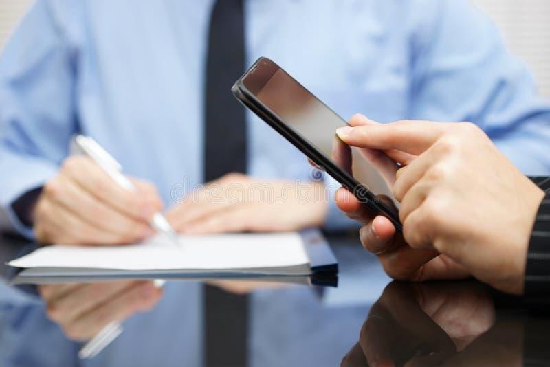 Geschäftsfrau verwendet bewegliches intelligentes Telefon und Geschäftsmann in BAC lizenzfreie stockfotografie
