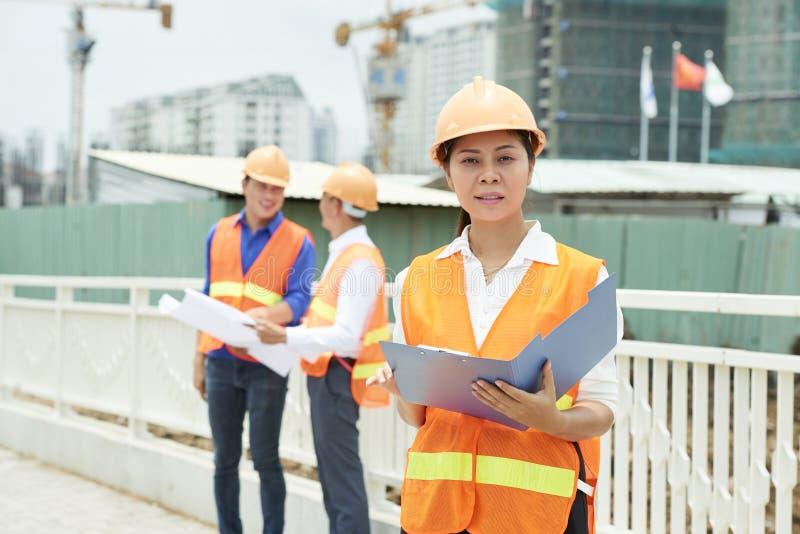 Geschäftsfrau, welche die Arbeit des Baus steuert lizenzfreie stockbilder