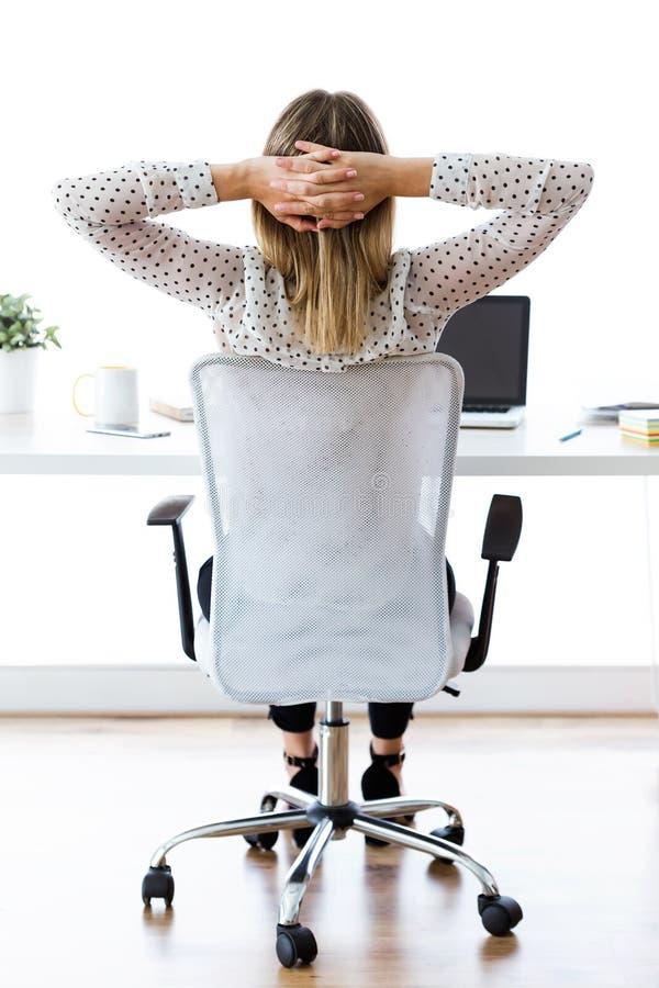Geschäftsfrau, welche die Entspannung auf Moment in ihrem Büro ausdehnt Zufriedengestellt mit Arbeit erfolgtem Konzept lizenzfreie stockfotos