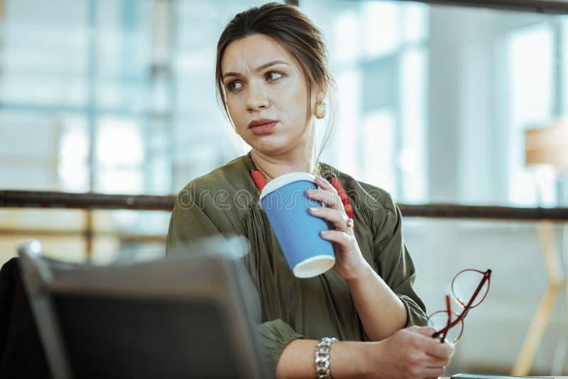 Geschäftsfrau, welche die stilvollen Ohrringe halten Tasse Kaffee trägt lizenzfreie stockfotografie