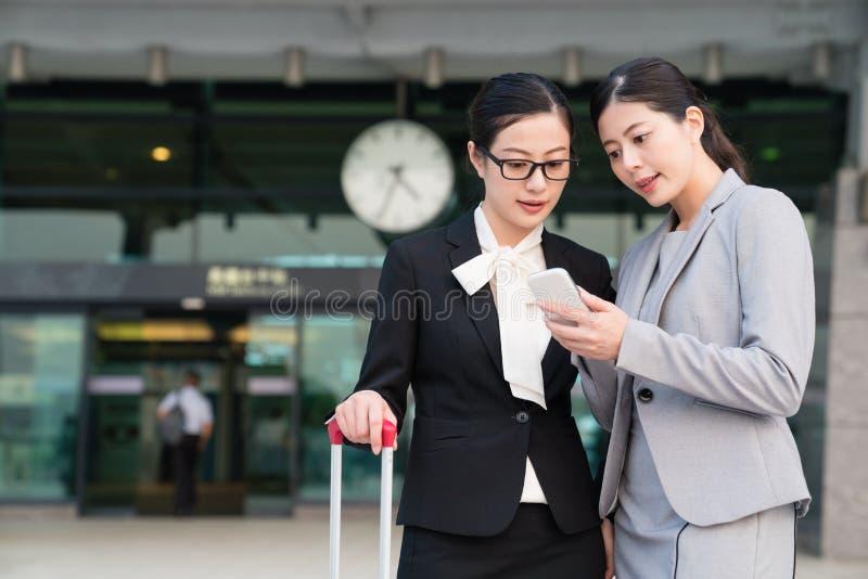 Geschäftsfrau, welche die Zeit durch Mobiltelefon zeigt lizenzfreies stockbild