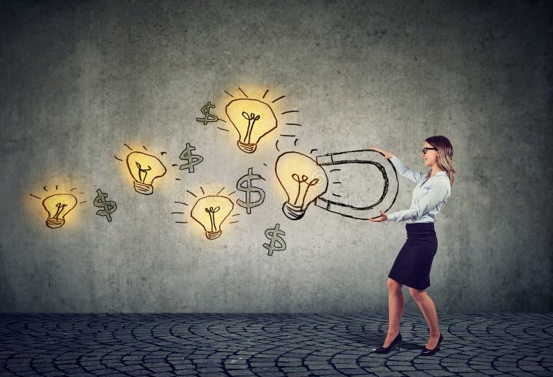 Geschäftsfrau zieht Glühlampen der guten Ideen mit einem großen Magneten an stockbilder