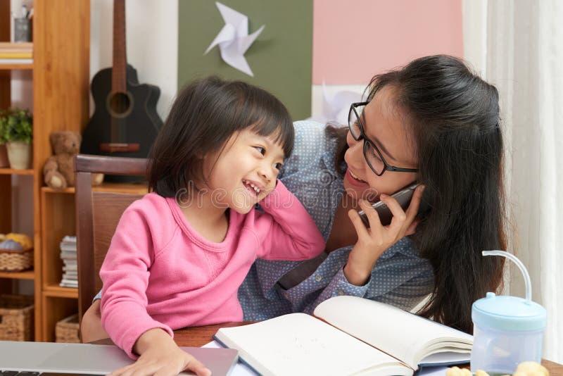 Geschäftsfrau zu Hause mit entzückender Tochter lizenzfreie stockbilder