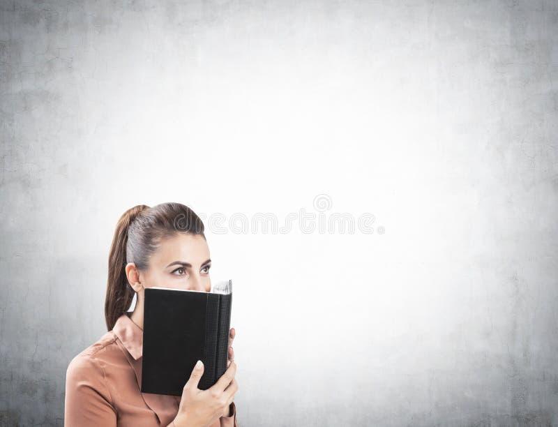 Geschäftsfraubedeckungsgesicht mit dem Planer, konkret lizenzfreies stockbild