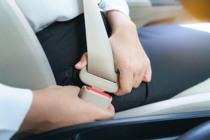 Geschäftsfraubefestigungs-Sicherheitsgurt im Auto bevor dem Fahren lizenzfreies stockfoto