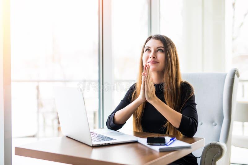 Geschäftsfraubeten Durchdachte Frau in formalwear Händchenhalten, das umklammert wird und oben nahe Laptop beim Sitzen betrachtet lizenzfreies stockfoto