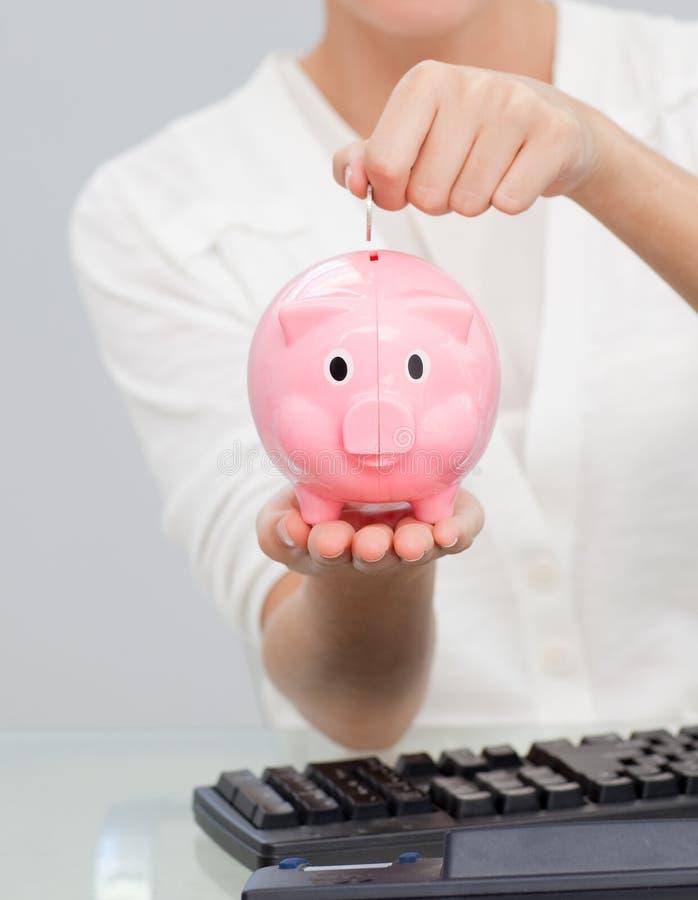 Geschäftsfraueinsparunggeld in einem piggibank lizenzfreie stockbilder