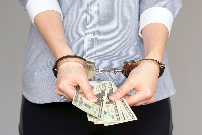 Geschäftsfrauen in den Handschellen mit einem Bestechungsgeld stockfotos