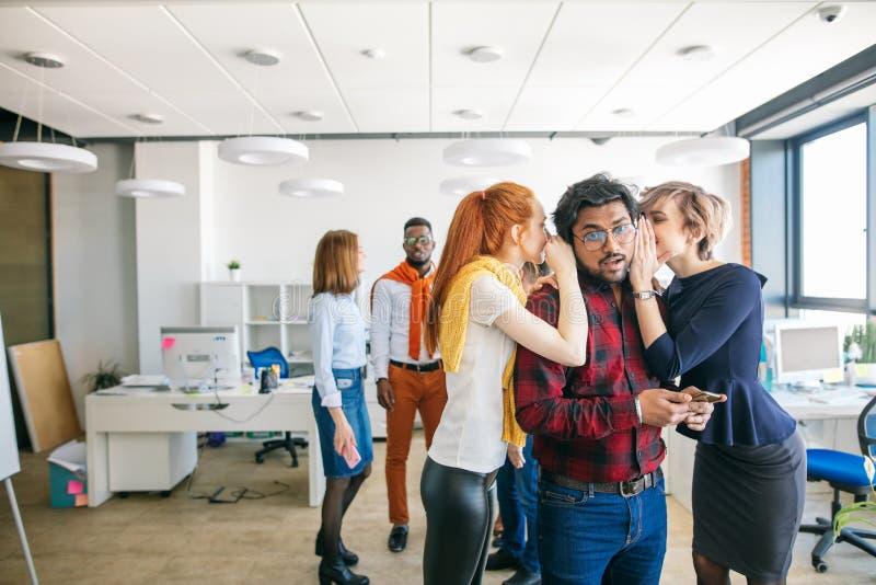 Geschäftsfrauen, die über Kollegen im Büro klatschen stockfoto
