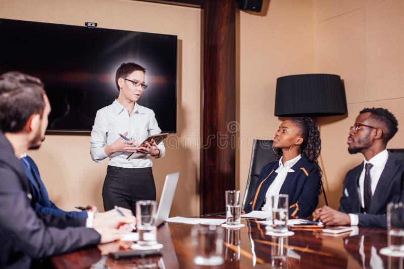 Geschäftsfrauen, die bei der Sitzung im modernen Büro aufeinander einwirken stockbild