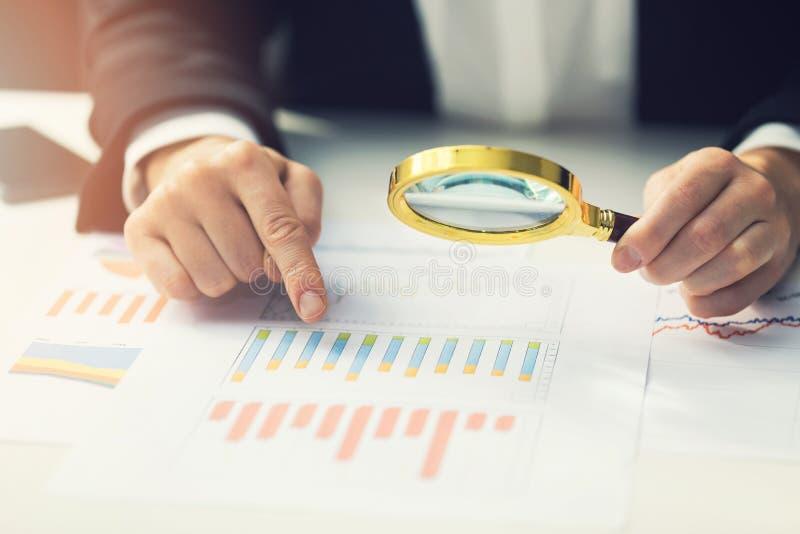 Geschäftsfrauen, die das Vergrößern, zum des Finanzberichts zu wiederholen verwenden stockbild