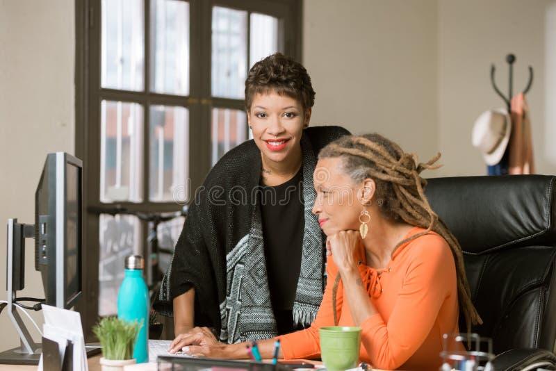Gesch?ftsfrauen, die in einem kreativen B?ro zusammenarbeiten stockfotografie