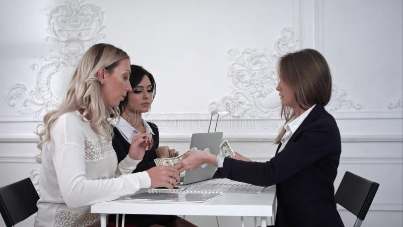 Geschäftsfrauen, die Geld im Büro empfangen stockfotos