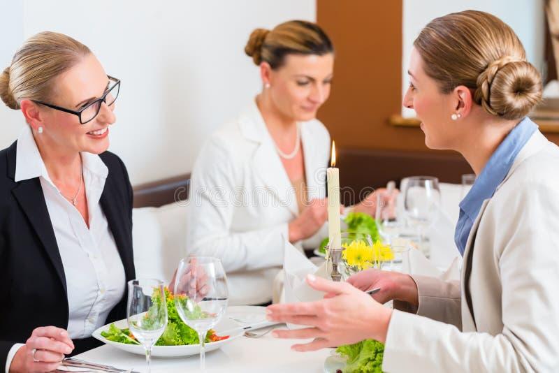 Geschäftsfrauen, die am Geschäftsabendessen sich treffen stockfotografie