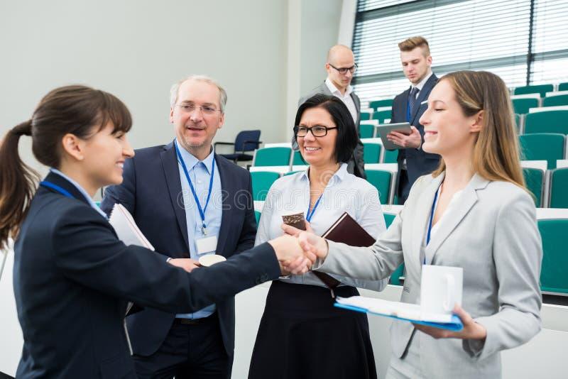Geschäftsfrauen, die Hände durch Kollegen in Vorlesungssal rütteln lizenzfreie stockbilder