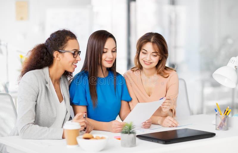 Geschäftsfrauen, die Papiere im Büro besprechen lizenzfreie stockfotografie