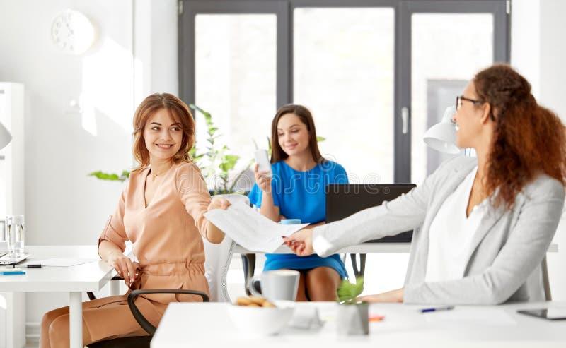 Geschäftsfrauen, die Papiere im Büro sich geben lizenzfreie stockfotografie