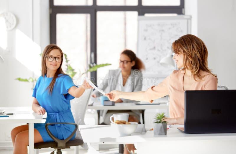 Geschäftsfrauen, die Papiere im Büro sich geben lizenzfreie stockbilder