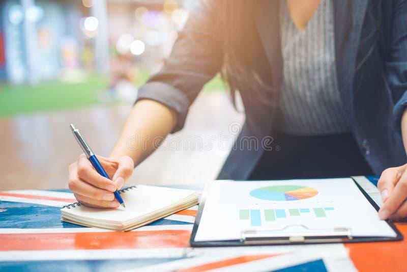 Geschäftsfrauen nehmen Kenntnisse über Wirtschaftsstatistik und Diagramme stockfoto