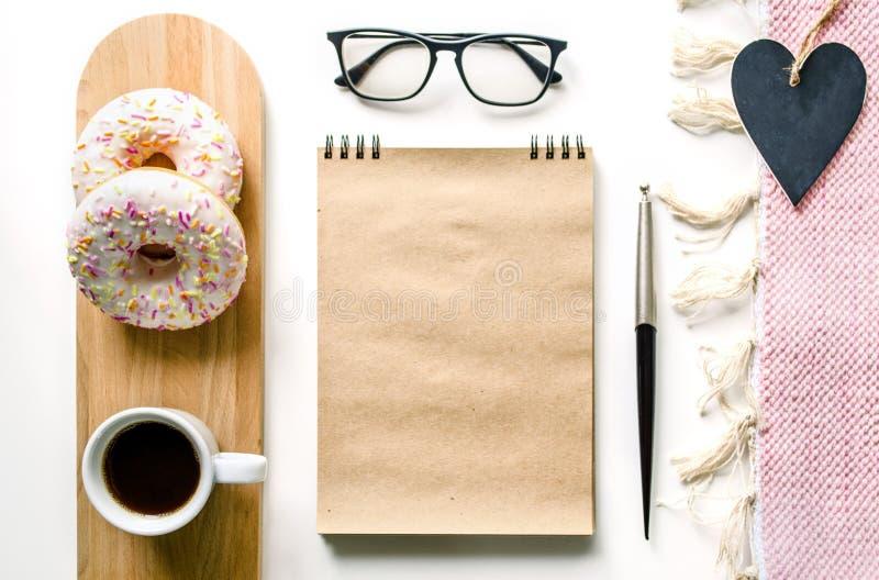 Geschäftsfrauen ` s Zusammensetzung mit Kaffee und Schaumgummiringen Snack am Schreibtisch Bürotischschreibtisch Innenministerium lizenzfreies stockfoto