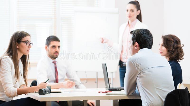 Geschäftsfrauen und Männer an der Darstellung im Büro lizenzfreies stockbild