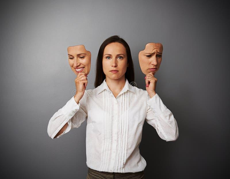 Geschäftsfraufrau, die zwei Masken hält stockbild
