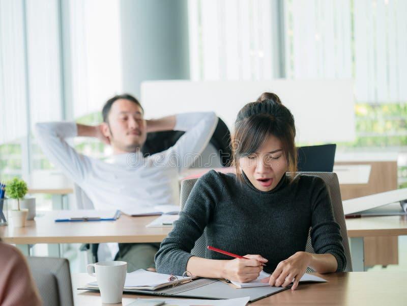 Geschäftsfraugegähne im Büro mit Geschäftsmann entspannt sich oder schläfrige an Rückseite lizenzfreie stockbilder