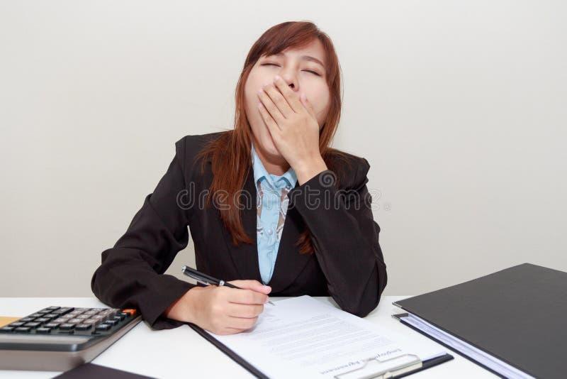 Geschäftsfraugegähne oder -gefühl schläfrig beim im Büro nachher arbeiten lizenzfreies stockbild