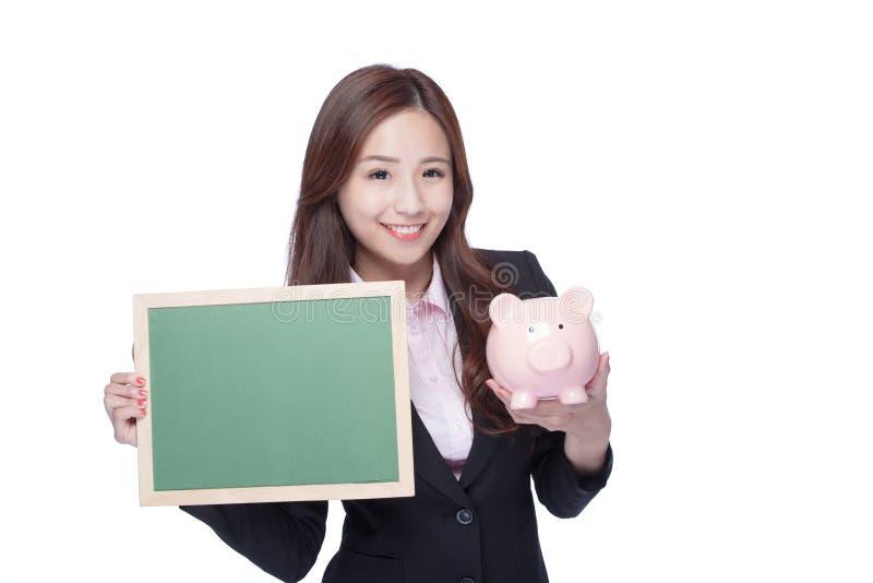 Geschäftsfraugrifftafel und piggy stockfoto