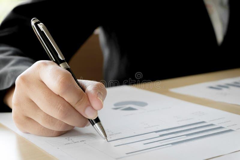 Geschäftsfrauhände, die Bewertung auf Datendokumenten analysieren stockfotografie