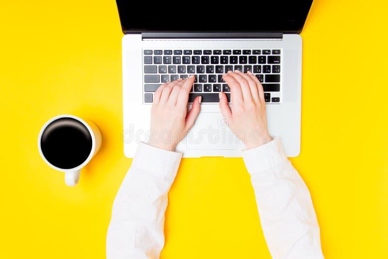 Geschäftsfrauhände mit Laptop und Tasse Kaffee stockbild