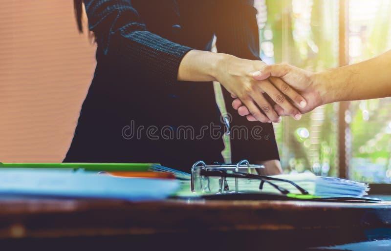 Geschäftsfrauhändeschüttelngeschäftsmänner folgen mit dem Job stockfoto