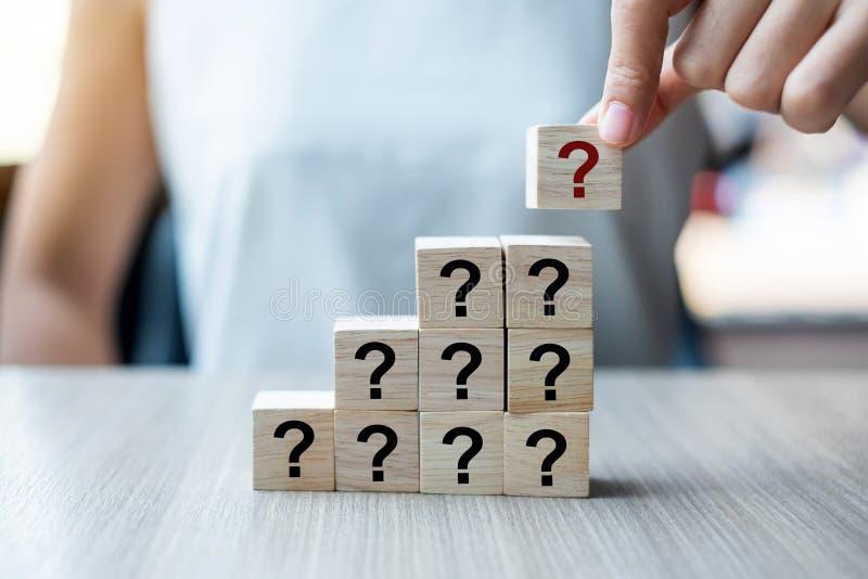 Geschäftsfrauhand, die Fragezeichen setzt oder zieht? Wort mit hölzernem Würfelblock auf dem Gebäude FAQ-Frequenz bat lizenzfreies stockfoto