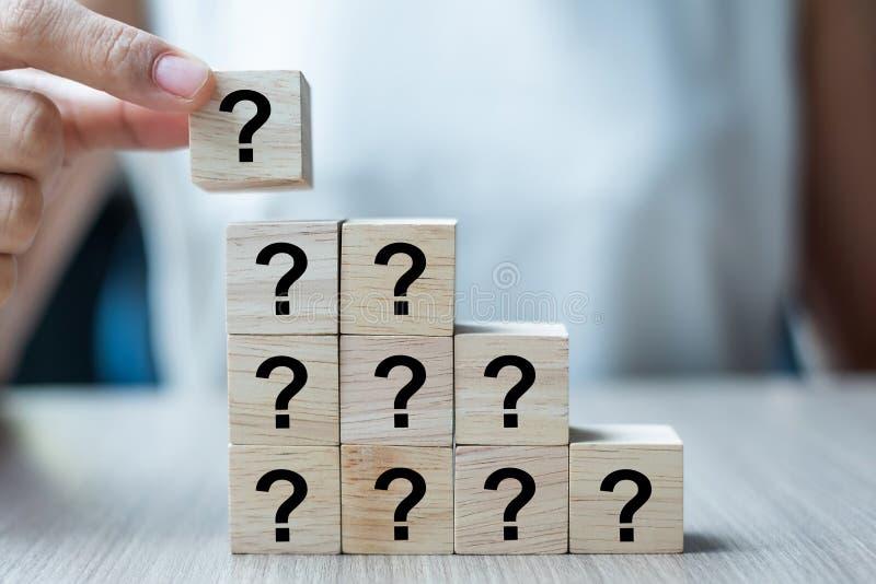 Geschäftsfrauhand, die Fragezeichen setzt oder zieht? Wort mit hölzernem Würfelblock auf dem Gebäude FAQ-Frequenz bat stockbild