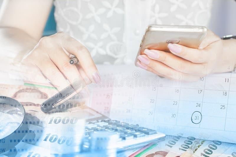 Geschäftsfrauhand, die intelligentes Telefon, Geld und calenda hält stockbilder