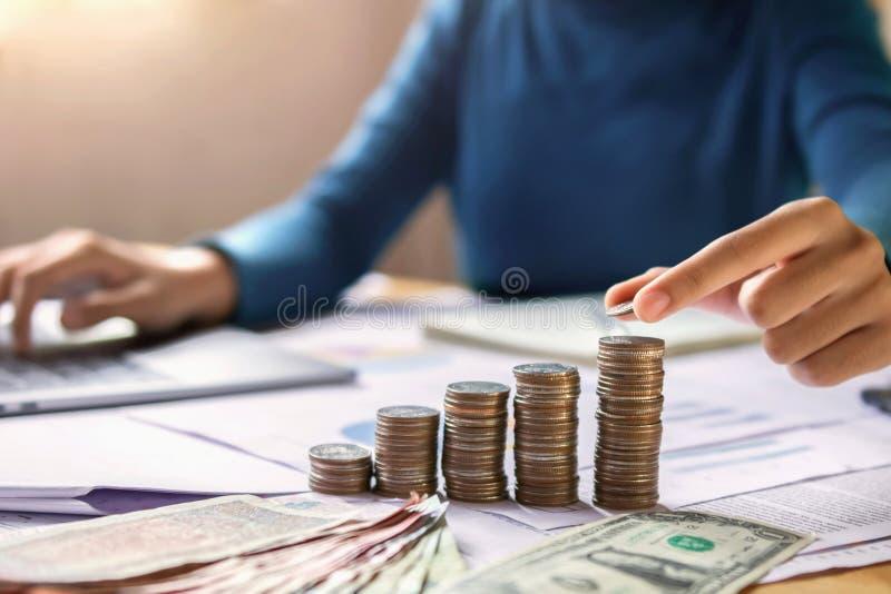 Geschäftsfrauhand, die Münzen hält, um auf Rettungsgeldfinanzierung des Schreibtischkonzeptes zu stapeln stockfotos