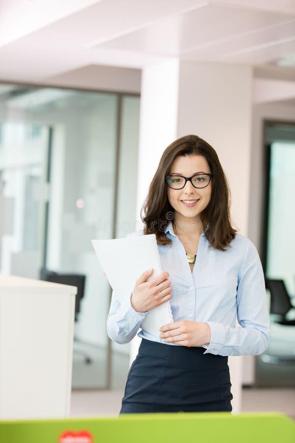 Geschäftsfrauholding-Spiralenbuch des Porträts schönes junges im Büro stockbilder