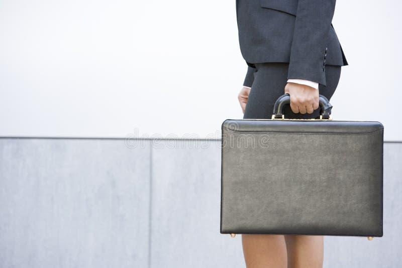 Geschäftsfrauholdingaktenkoffer draußen stockfotos
