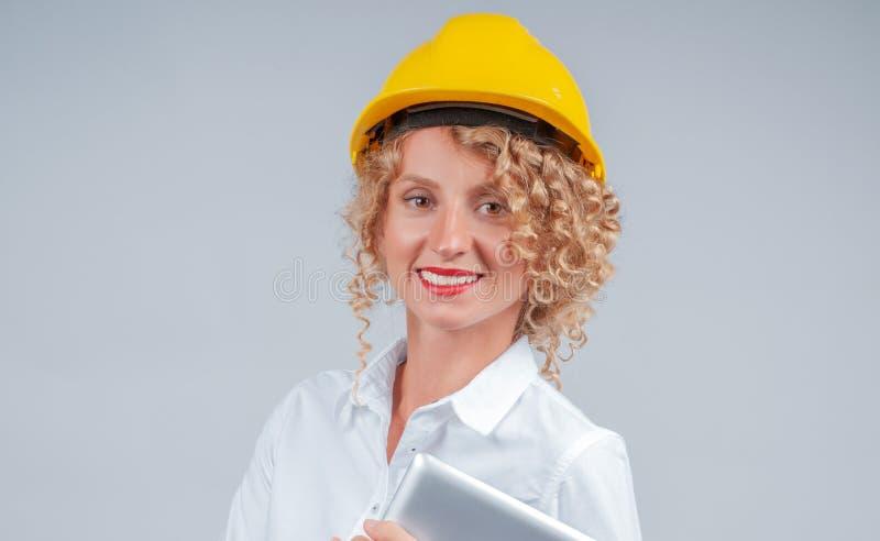 Geschäftsfrauingenieur im gelben Schutzhelm mit Tablette lizenzfreies stockbild