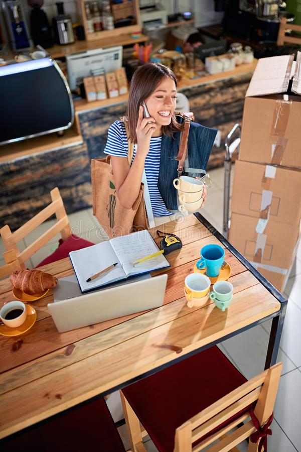 Geschäftsfrauinhaber, der mit dem Laptop bereit, ihr Café zu öffnen arbeitet stockfotografie