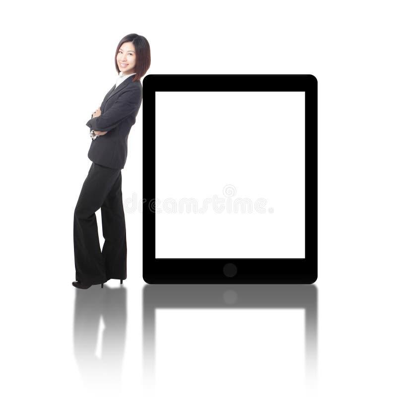 Geschäftsfraulächeln, das mit Tablette-PC steht lizenzfreie stockbilder