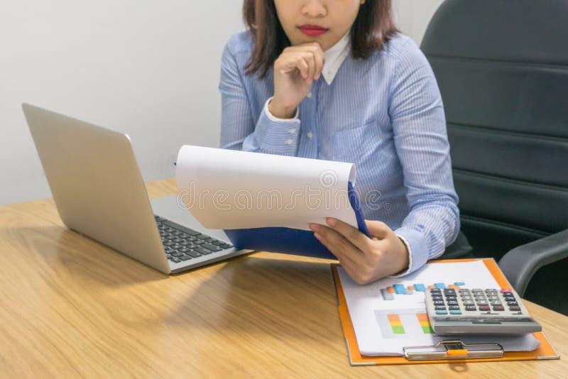 Geschäftsfraulesende Finanzzahl auf dem Finanzdokument stockfotos