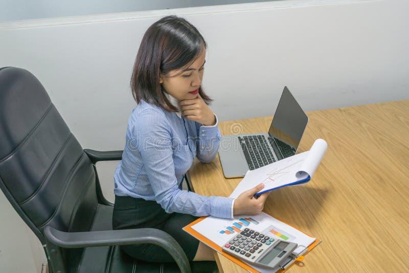 Geschäftsfraulesende Finanzzahl auf Dokumentenbericht lizenzfreie stockfotos